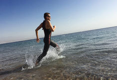Professional Triathlete Practicing In Open Water. Plunge In Sea.