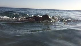 Professional triathlete practicing in open water. Swimming in se