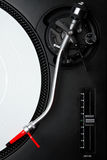 Professional turntable for a DJ. Professional DJ audio equipment - turntable needle on white vinyl record shot from above Royalty Free Stock Image
