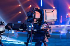 A television camera on the recording of a concert. Professional TV camera with a large lens on the tripod during the recording of the concert stock images