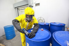 Professional in uniform dealing with chemicals. Fully protected in yellow uniform,mask,and gloves professional filling barrel with chemicals stock image