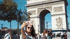 Professional video of beautiful female taking selfie while on urban street with Arc de Triomphe behind her. Paris in stock video footage