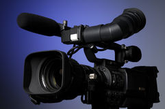 Professional video camera. On a blue background Stock Images