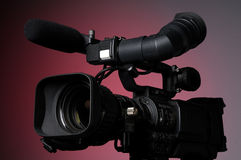 Professional Video Camera. Against a red background Royalty Free Stock Image