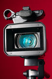 Professional video camera. On a red background Royalty Free Stock Photos
