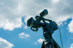 Professional video camera. On a tripod against the blue sky Royalty Free Stock Image