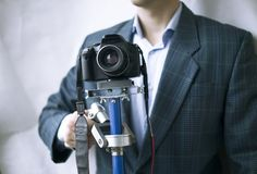 Professional videographer keeps steadicam with camera on white background. stock images
