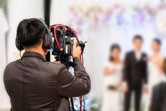 Professional videographer recording wedding ceremony day. With professional camcoder and boardcasting Royalty Free Stock Image