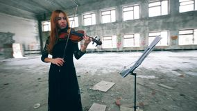 Professional violinist plays by notes in a big room of abandoned building. 4K stock video footage