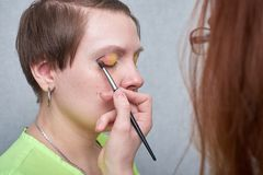 Professional visage artist applying color makeup on woman`s face on grey background. stock photo