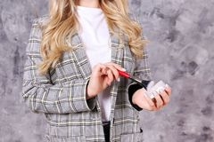 Professional visagiste posing with her equipment over grunged concrete wall background. Young beautiful makeup artist w/ long curly hair wearing fashionable royalty free stock image