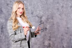 Professional visagiste posing with her equipment over grunged concrete wall background. Young beautiful makeup artist w/ long curly hair wearing fashionable royalty free stock images