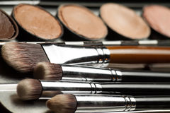 Professional visagiste workspace. Cream concealer palette in metal case. Expensive makeup brushes made of special fibers to work with creamy textures. Working Royalty Free Stock Image