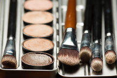 Professional visagiste workspace. Cream concealer palette in metal case. Expensive makeup brushes made of special fibers to work with creamy textures. Working Royalty Free Stock Photography