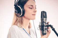 Professional Voice Talent. Female Voice Talent in the Recording Studio. Closeup Photo. Girl Recording Her Voice Using Professional Microphone Royalty Free Stock Image