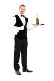 Professional waiter holding a tray with champagne. Full length portrait of a professional waiter holding a tray with a champagne and two glasses on it isolated Royalty Free Stock Image