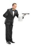 Professional waiter holding a tray. Full length portrait of a professional waiter holding a tray isolated on white background Stock Image