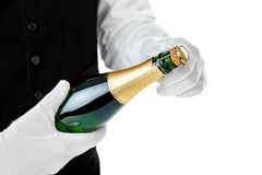 Professional waiter opening bottle of champagne. Isolated on white background Stock Photography