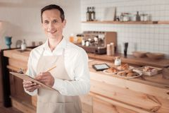 Pleasant nice man taking the order. Professional waiter. Pleasant nice taking the order while working as a waiter in the cafeteria Stock Photography