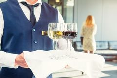 Professional waiter in uniform holding a tray with glasses of vine at business event. Catering or celebration concept. Service at. Corporate meeting, party Royalty Free Stock Images