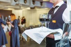 Professional waiter in uniform holding a tray with glasses of vine at business event. Catering or celebration concept. Service at. Corporate meeting, party Royalty Free Stock Photography