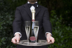 Professional waiter in uniform is serving champagne Stock Photography