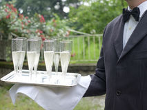 Professional waiter in uniform is serving champagne Stock Images