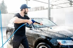Man washing car with water gun. Professional washer in black uniform washing luxury car with water gun on an open air car wash royalty free stock images