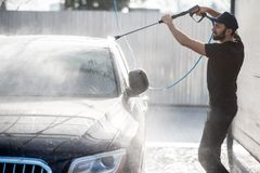 Man washing car with water gun. Professional washer in black uniform washing luxury car with water gun on an open air car wash stock photo