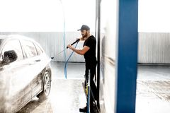 Man washing car with water gun. Professional washer in black uniform washing luxury car with water gun on an open air car wash stock photography