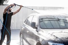 Man washing car with water gun. Professional washer in black uniform washing luxury car with water gun on an open air car wash royalty free stock image