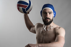 Professional water polo player shooting ball looking at camera Stock Photography