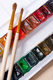 Professional watercolor paints in box with brushes. Close up view of the professional aquarelle paints in box with brushes on the wooden background stock photography