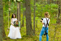 Wedding photographer taking pictures of the bride on a rope swing stock image