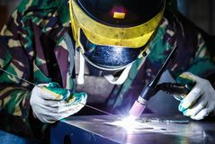 Welder welding with electric torch tool. Professional welder in mask welds steel with electric welding torch tool.Factory worker welding metal parts with burner royalty free stock photography