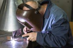 Professional welder welding metal parts Stock Photography