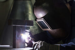 Professional welder welding metal parts. In steel construction company Royalty Free Stock Images