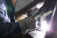 Professional welder welding metal parts. In steel construction company Stock Photo