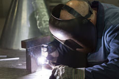 Professional welder welding metal parts. In steel construction company Royalty Free Stock Photos