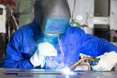 Professional welder welding metal pieces in steel construction Royalty Free Stock Image