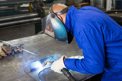 Professional welder welding metal pieces in steel construction. Professional welder welding metal pieces with light arc and sparks Royalty Free Stock Image
