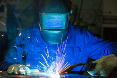 Professional welder welding metal pieces in steel construction. Professional welder welding metal pieces with light arc and sparks Royalty Free Stock Images