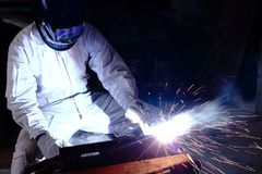 Professional welder welding steel with spark in workshop with copy space background. Industrial concept. Royalty Free Stock Photo
