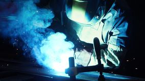 Professional welder working with argon-arc welding at plant. Technician welding