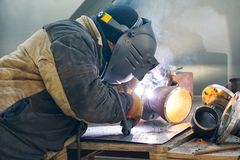 Manual electric arc welding of the junction Du 100 and flange stock image
