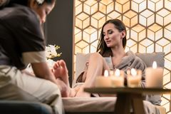 Therapist massaging the foot of a female client in Asian beauty Royalty Free Stock Image