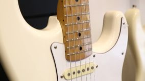 Professional white electric guitar. Bottom-up movement