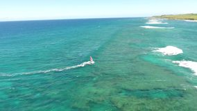 Professional widsurfing in calm turquoise blue ocean water calm white foamy waves in amazing 4k aerial drone seascape. Professional widsurfing in calm turquoise stock video footage