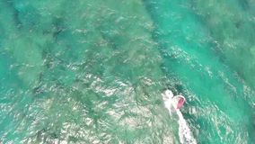 Professional windsurfer gliding in calm waves of turquoise blue ocean water Hawaiian seascape in top 4k aerial drone cam. Professional windsurfer gliding in calm stock video footage