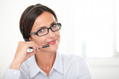 Professional woman conversing on her headphones Stock Images